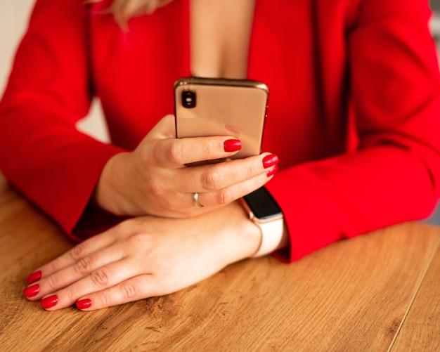 Close up van een vrouw in rood pak met behulp van mobiele slimme telefoon. blogger met rode manicure