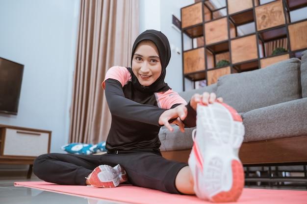 Close-up van een vrouw in sportkleding hijab glimlacht terwijl ze een been opzij strekt en het met een hand vasthoudt