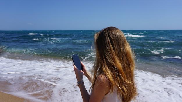 Close-up van een vrouw met behulp van mobiele telefoon, strand en zee op de achtergrond. vrouwen gebruiken mobiele app