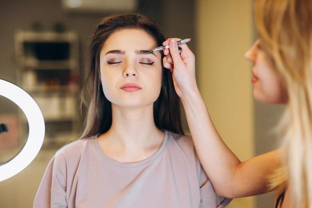 Close-up van een vrouw met bruin haar die make-up krijgt. make-upborstel dichtbij het gezicht. visagist maakt gekleurde wenkbrauwen of borstel wenkbrauwen.