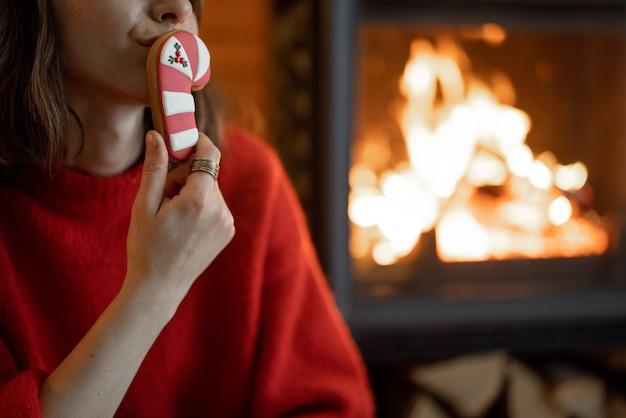 Close-up van een vrouw met een kerstsnoep bij de open haard. warmte en gezelligheid tijdens de wintervakantie thuis