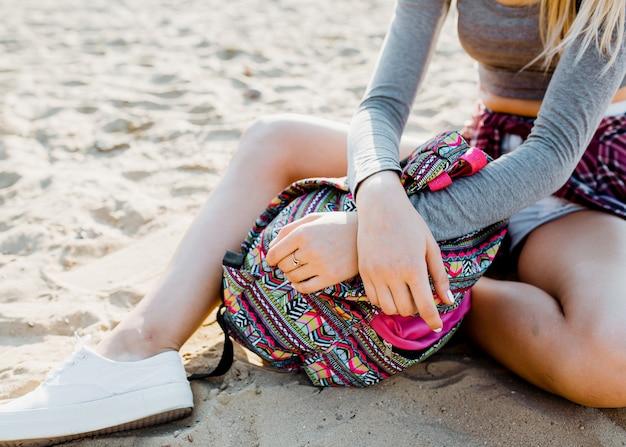 Close up van een vrouw met een kleurrijke rugzak, zittend op zand op het strand