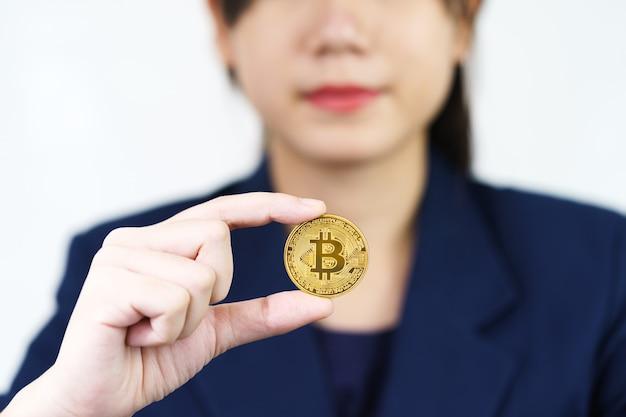 Close-up van een vrouw met een paar stukjes gouden bitcoin-token
