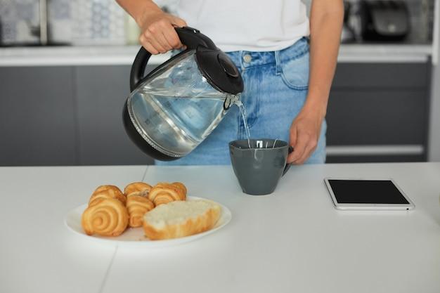 Close-up van een vrouw staat in de buurt van de tafel, houdt een glazen theepot vast en zet thee in een groot grijs theekopje