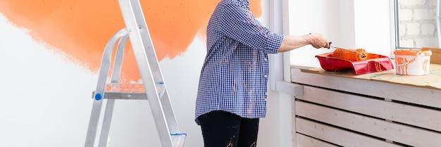 Close-up van een vrouw van middelbare leeftijd die de muur schildert met een verfroller. portret van een jonge mooie vrouw die muur in haar nieuwe appartement schildert. herinrichting en renovatie concept.