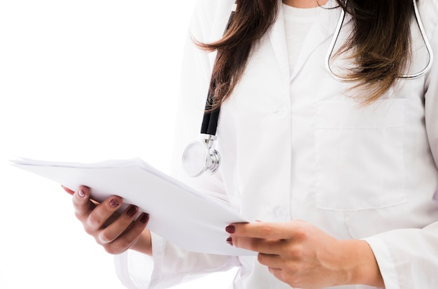 Close-up van een vrouwelijke arts die het medische die rapport houdt ter beschikking op witte achtergrond wordt geïsoleerd
