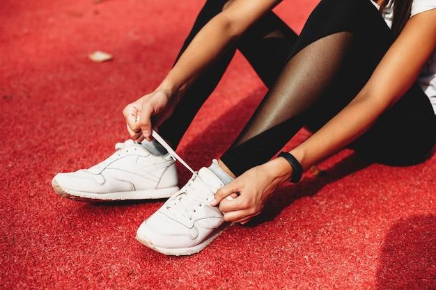 Close-up van een vrouwelijke benen zittend op de grond in het sportpark schoenveters binden voor het hardlopen.