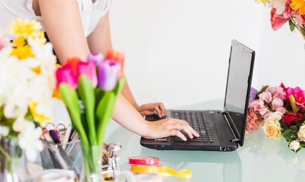 Close-up van een vrouwelijke bloemisthand die aan laptop werkt
