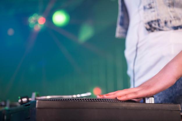 Close-up van een vrouwelijke dj-hand op een record in nachtclub