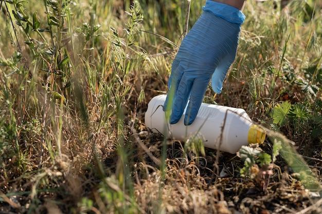 Close-up van een vrouwelijke hand in een rubberen handschoen. vrijwilligers verzamelen afval in het park. plastic afval. milieuvervuiling
