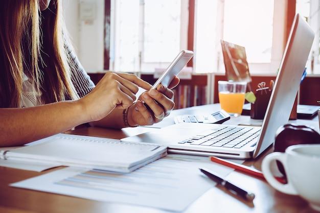 Close-up van een vrouwelijke hand met behulp van een slimme telefoon met laptop op een bureau op kantoor