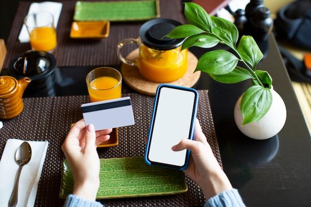 Close-up van een vrouwelijke handen - vrouw kaart betaling via mobiele telefoon om rekeningen te betalen. uitzicht vanuit de ogen.