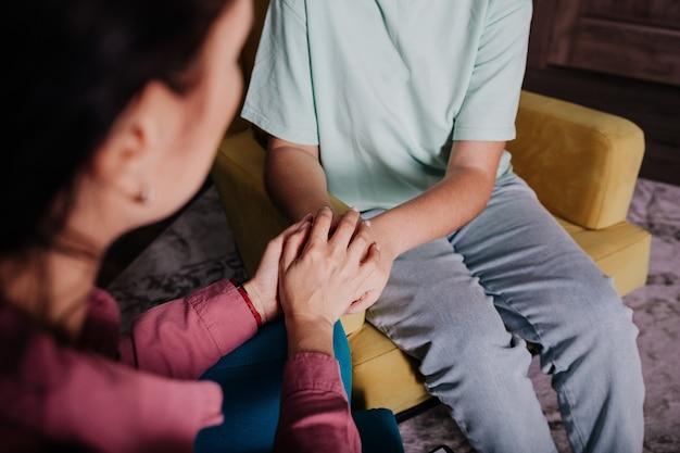 Close-up van een vrouwelijke psycholoog die de handen van de patiënt omhelst in een gebaar van steun