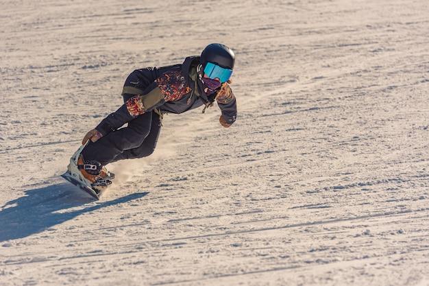 Close-up van een vrouwelijke snowboarder in beweging op een snowboard in een berg