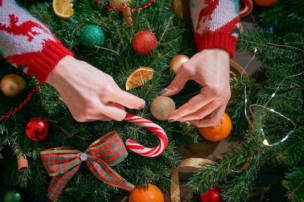 Close-up van een vrouwenhanden die met de hand gemaakte kerstmiskroon maken op lijst voor vakantie.