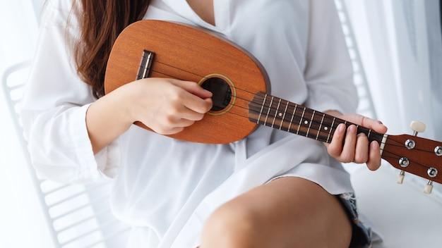 Close-up van een vrouwenzitting en het spelen ukelele in slaapkamer