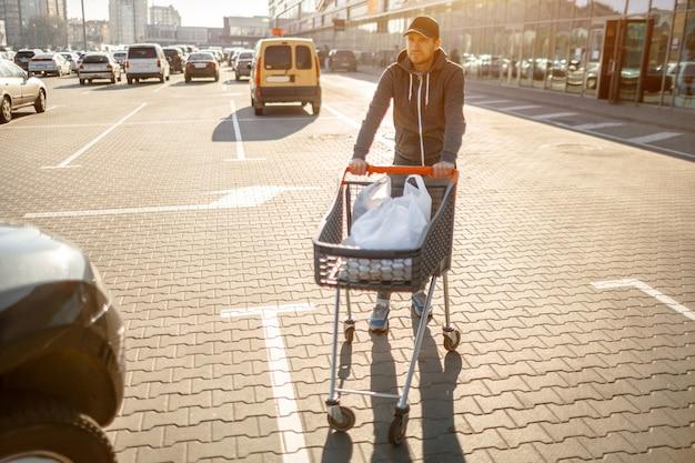 Close-up van een wandelwagen met voedsel dichtbij een grote supermarkt in een winkelcentrum in de voorsteden.