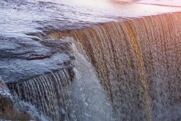 Close-up van een waterval die het vlotte tuimelende water toont.
