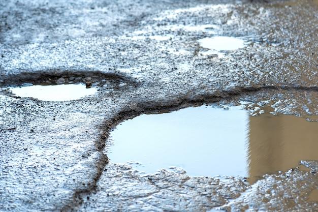Close up van een weg in zeer slechte staat met grote kuilen.