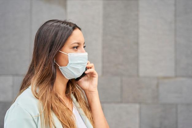 Close-up van een werkende vrouw die met gezichtsmasker aan de telefoon spreekt. aan de rechterkant is er een lege ruimte om tekst te integreren. de achtergrond is een grijze muur.