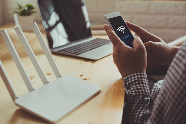 Close-up van een wifi-router en een man met behulp van een smartphone