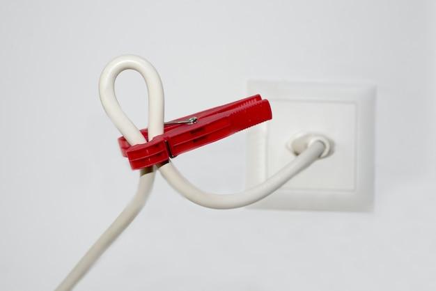 Close-up van een witte kabel en een rode wasknijper