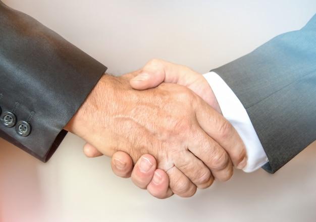 Close-up van een zakelijke handdruk tussen twee zakenlieden in pakken,