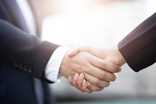 Close-up van een zaken man hand schudden zakenvrouw tussen twee collega's ok, slagen in het bedrijfsleven hand in hand.