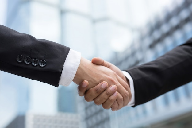 Close-up van een zakenman die de hand schudt tussen twee collega's