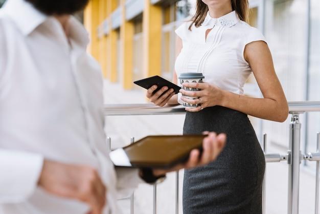 Close-up van een zakenman die digitale tablet in hand met onderneemster houdt die zich op de achtergrond bevindt