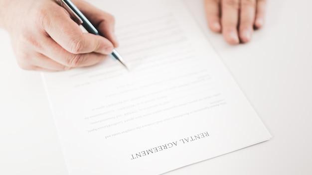 Close-up van een zakenman die een huurovereenkomst met een pen ondertekent.