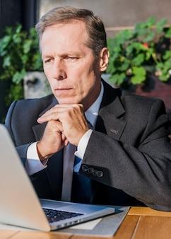 Close-up van een zakenman die laptop het scherm bekijkt