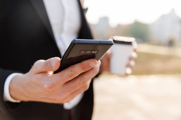 Close up van een zakenman die mobiele telefoon buitenshuis gebruikt, met een koffiekopje om mee te nemen