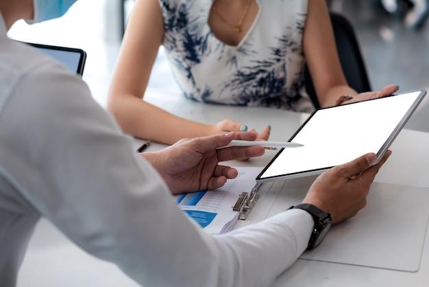 Close-up van een zakenman die op een tablet werkt met een leeg wit scherm op kantoor.