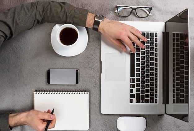 Close-up van een zakenman die op klembord schrijft die digitale tablet op bureau gebruikt
