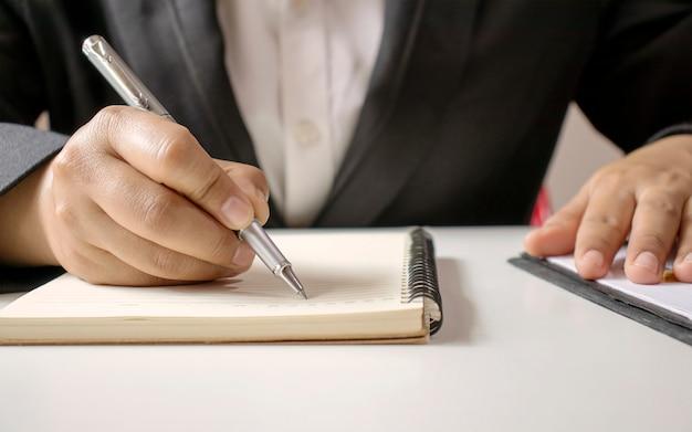 Close-up van een zakenman die pen gebruikt om te schrijven