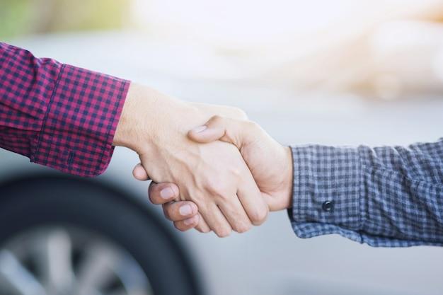 Close-up van een zakenman hand schudden investeerder tussen twee collega's ok, slagen in het bedrijfsleven hand in hand.