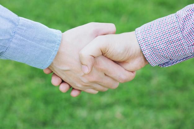 Close up van een zakenman hand schudden tussen twee collega's begroeten, vertegenwoordigt vriendschap is goed, succes, gefeliciteerd. kopie laat ruimte voor tekst.