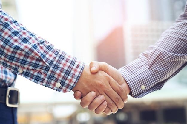 Close-up van een zakenman hand schudden tussen twee collega's ok, slagen in zaken hand in hand. laat ruimte over om een beschrijving van het bericht te schrijven.