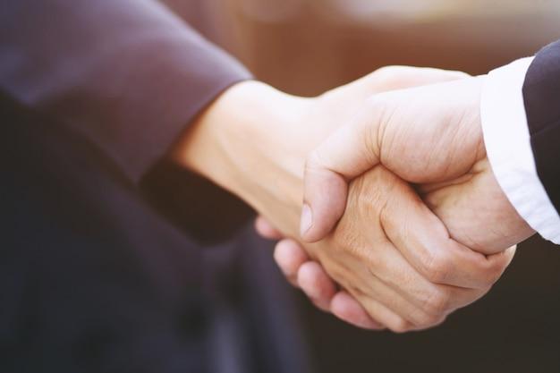 Close up van een zakenman jonge knappe hand schudden tussen twee collega's. of onderhandelde overeenkomst succesvolle baan.