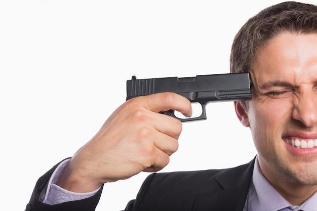 Close-up van een zakenman met een pistool tegen het hoofd