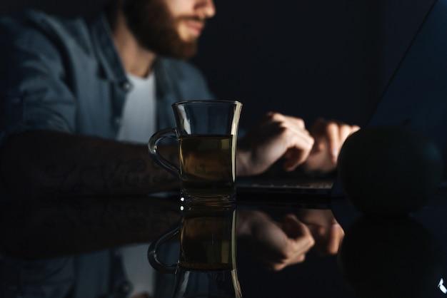 Close-up van een zelfverzekerde jonge man die op een laptop werkt terwijl hij 's nachts binnenshuis aan tafel zit