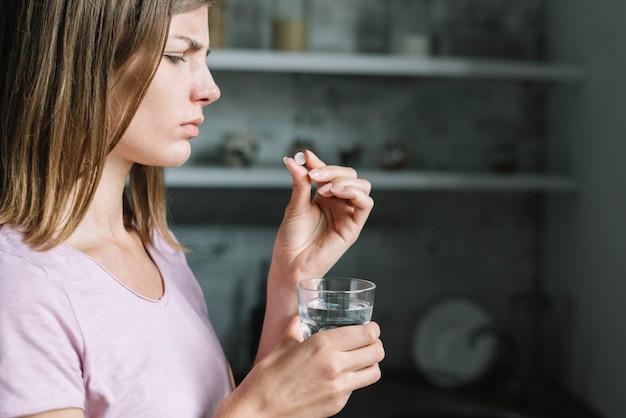 Close-up van een zieke jonge vrouw met pil en een glas water