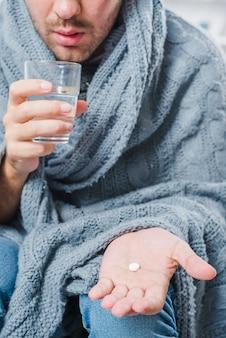 Close-up van een zieke man met witte pil in zijn hand en waterglas te houden