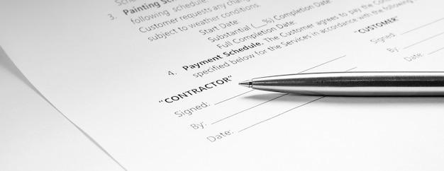 Close-up van een zilveren pen op documentcontract. ondertekening van een wettelijk contract. koop verkoop onroerend goed contract overeenkomst.