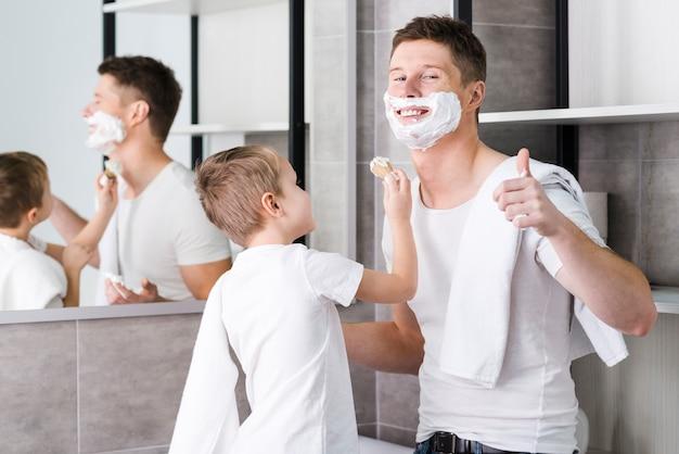 Close-up van een zoon die zijn vader voor het scheren van baard helpt die duim op toont
