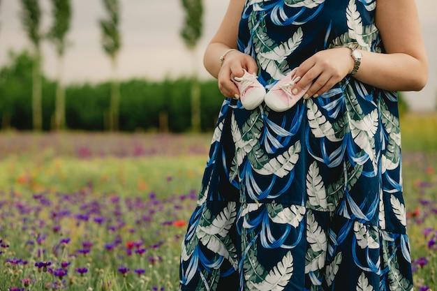 Close-up van een zwangere vrouw die geniet van het toekomstige moederschap en haar babyschoenen vasthoudt en in het veld staat