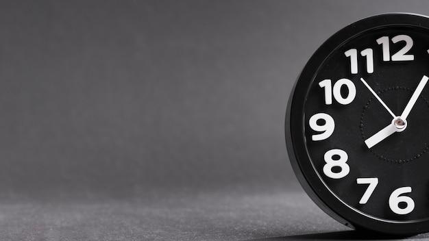 Close-up van een zwarte klok tegen een grijze achtergrond