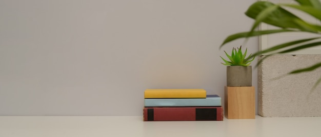 Close-up van eenvoudige studie tafel met kopie ruimte, boeken, plant vaas en decoraties op witte tafel