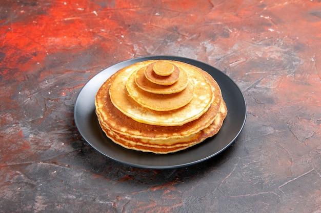 Close-up van eenvoudige zelfgemaakte pannenkoeken in een zwarte plaat